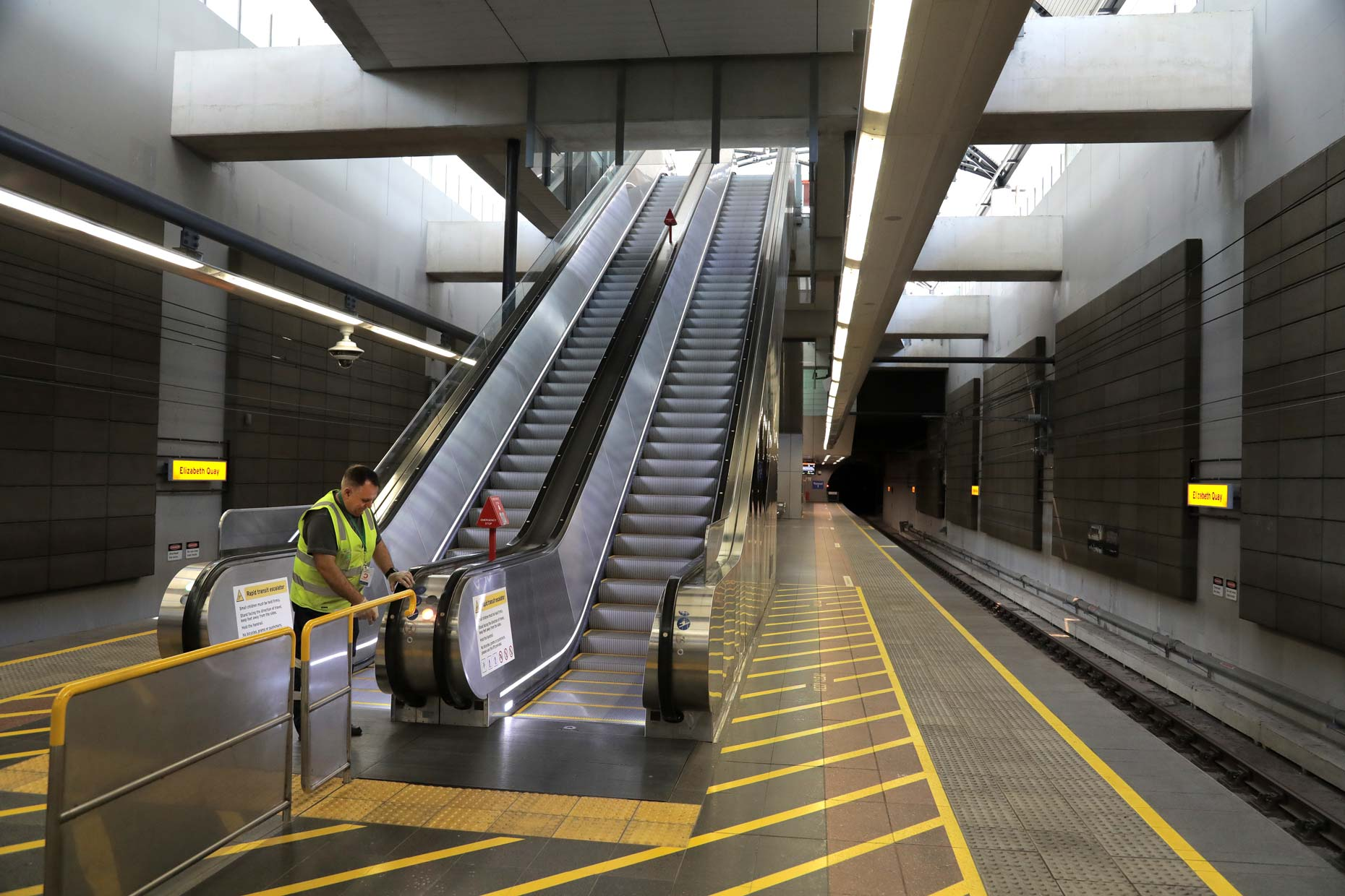 A cleaner sanitisers escalator handrail during COVID-19 lockdown